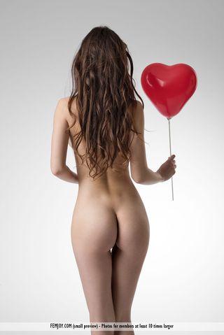 Модель с красной подвеской в студии снимается для интимных фото нагишом