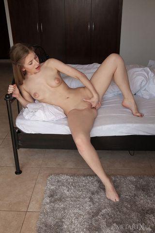 Девка сидит на сером коврике с раздвинутыми ногами и таранит пальчиками вагину