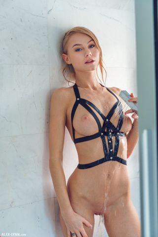 Модель в душевой комнате поливает теплой водой стоячие сиси и бритое влагалище