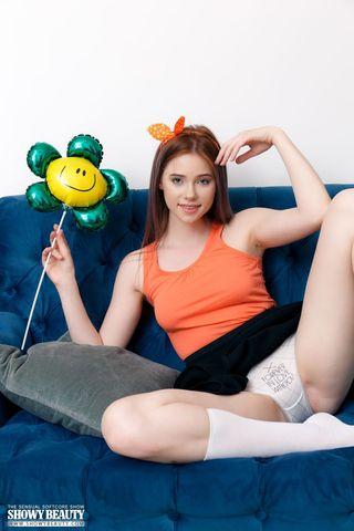 Девушка на синем диване с воздушными шариками позирует без трусов