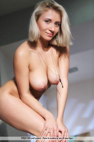Модель с висячей грудью снимает откровенные фотографии на полу комнаты