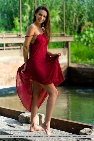 Смуглая девушка снимает бордовое платье на лужайке и светит стоячими сисями и писюшкой
