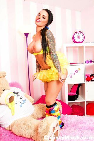 Брюнетка с татуированным телом позирует в коротком желтом платье без трусиков