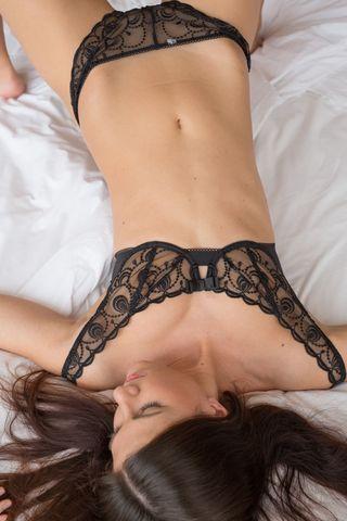 Стройная фотокрасотка раздевается в кровати и гладит руками нежные сиси
