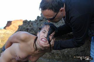 Мужик вывел на берег секс-рабыню с кляпом во рту и снял ее голой со всех сторон