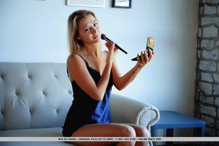Девушка снимает синий пеньюар и занимается созданием интимных фотографий