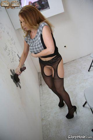 Девка на шпилях через отверстие в стене дрочит и сосет два черных фаллоса
