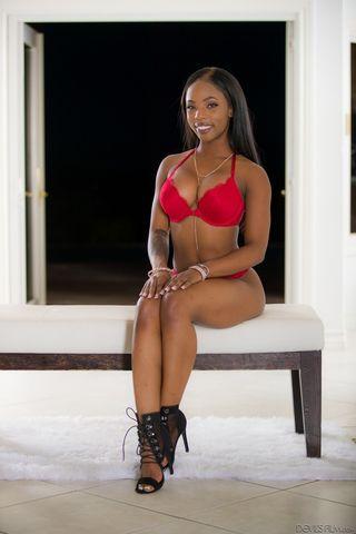 Негритянка в черных туфлях показывает фотографу упругие сиськи с пирсингом сосков