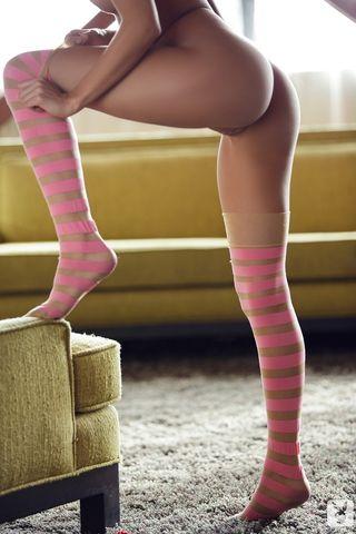 Худышка в розовых полосатых гетрах разминает пальчиками писю во время йоги